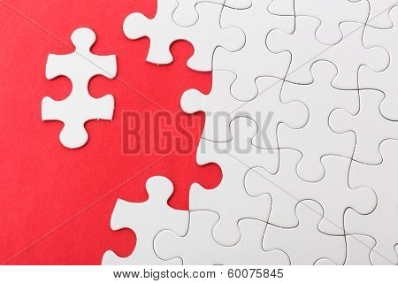 Incompleted white puzzle on red background