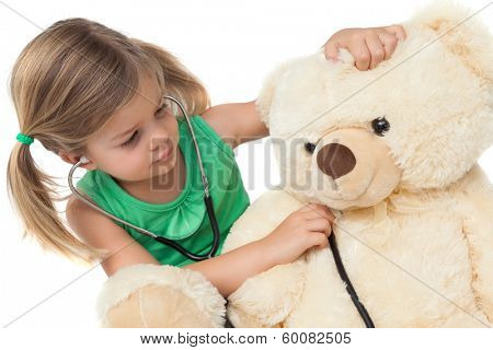 Cute little girl playing doctor with her teddy bear on white background