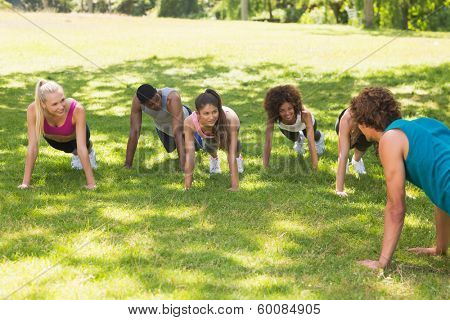 Instructor with group of fitness class doing push ups in the park