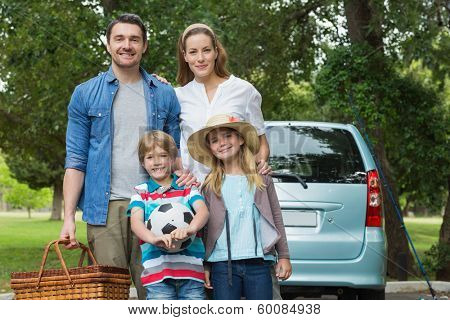 Portrait of a happy family of four with car at picnic