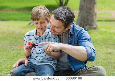 Young boy with toy aeroplane sitting on father's lap at the park