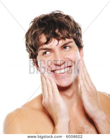 Happy Man Applying Moisturizing Cream After Shaving