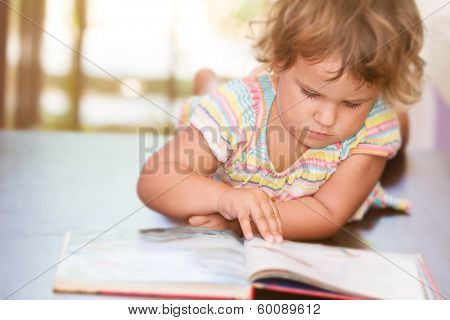 cute child girl reading a book at home or classroom