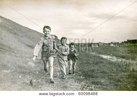 POLAND, CIRCA FORTIES - Vintage photo of children running outdoor with a stick toy