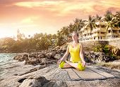 foto of guest-house  - Woman doing yoga meditation in yellow costume on the stone nearby ocean and tropical resort in Kovalam Kerala India - JPG
