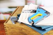 stock photo of staples  - Construction stapler with fabrics and staples on wooden box on bright background - JPG