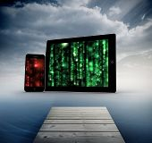 Matrix on tablet and smartphone screens against cloudy sky over ocean