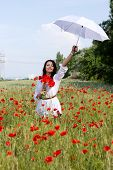 Portrait Of The Beautiful Girl In A Poppy Field With An Umbrella