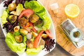 stock photo of sauteed  - Mixed salad greens with sauteed brussels sprouts tomato and radish drizzled with virgin olive oil and lemon dressing and served in a dish overhead view - JPG