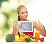 fitness, diet, technology, health and food concept - sporty woman with fruits and vegetables pointin