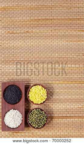 sesames and green beans in small bowls with empty space mat background