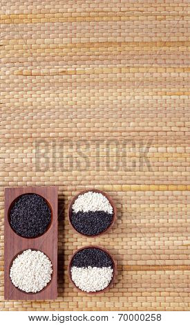 sesames in small wooden bowl with empty space mat background