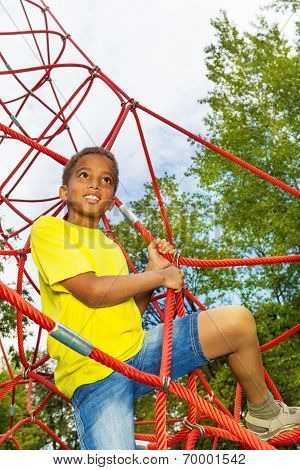 Looking boy holds and climbs on red ropes