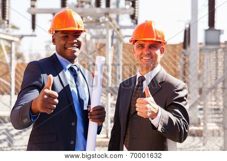 portrait of electrical inspectors giving thumbs up at substation