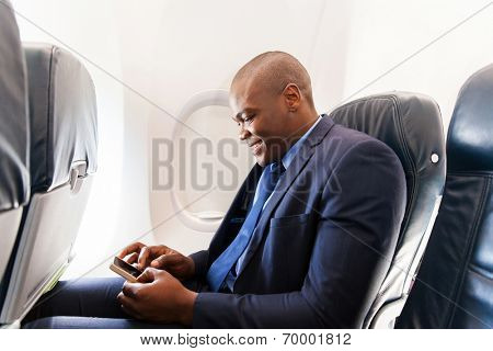 happy african airplane passenger using smart phone on plane