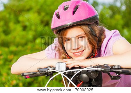 Portrait of smiling girl in helmet on handle-bar