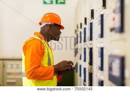 professional african power company technical worker in control room