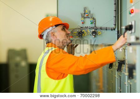 professional senior technician checking industrial machine control box