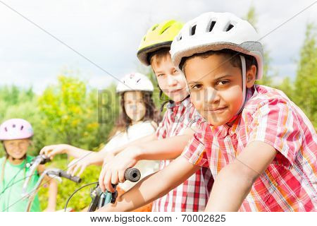 Small looking African boy in helmet with friends