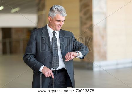 good looking mid age businessman checking time at airport