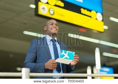 young african businessman holding air ticket at airport