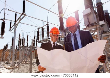 power company managers discussing blueprint at electrical substation