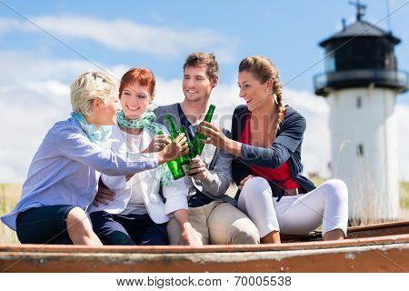 Friends drinking bottled beer enjoying vacation at German north sea beach