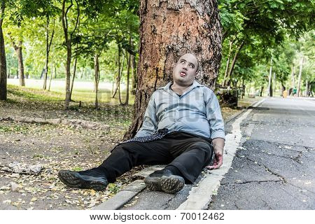 A fat Asian guy corpse die under the tree beside the street