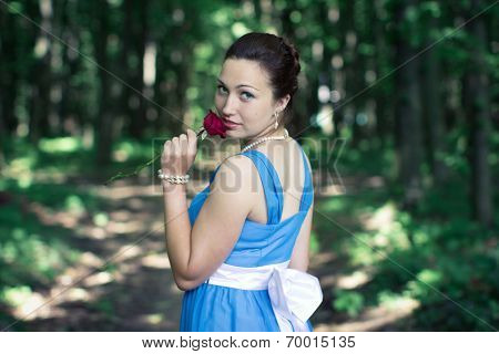 Girl Turns Around With Red Rose In Her Hand In The Dark Forest
