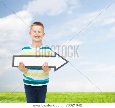 advertising, direction, environment and childhood concept - smiling little boy with white blank arrow pointing up over natural background