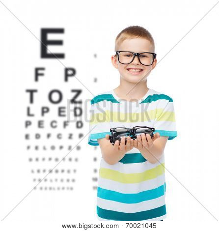 vision, health, ophthalmology and people concept - smiling little boy in eyeglasses holding spectacles over eye chart background