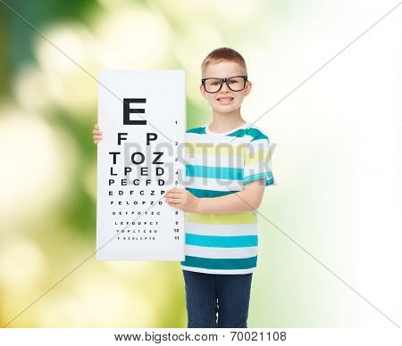 vision, health, ecology, ophthalmology and people concept - smiling little boy wearing eyeglasses with white blank board over green background