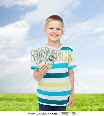 financial, planning, childhood and environment concept - smiling boy holding dollar cash money in his hand over natural background