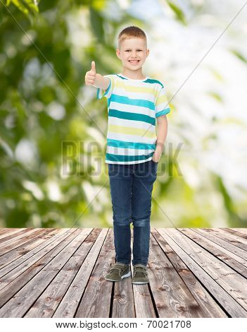 childhood, summer, gesture and people concept - smiling little boy showing thumbs up over plants and wooden floor background