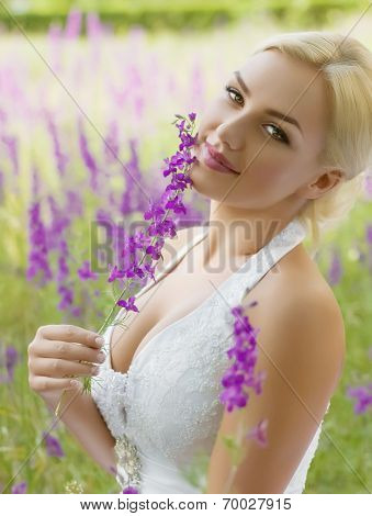 Portrait of beautiful bride with violet flowers