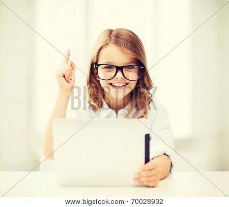 education, school, technology and internet concept - little student girl in black eyeglasses with tablet pc computer and finger up at school