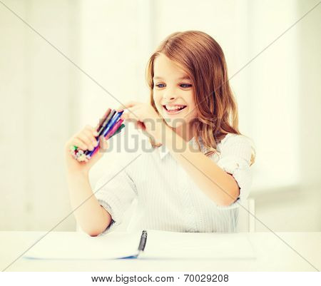education, creation and school concept - smiling little student girl choosing colorful felt-tip pen at school