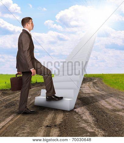 Businessman climbing up stairs leading to sky