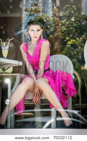 Fashionable attractive young woman in pink dress sitting in restaurant, beyond the window