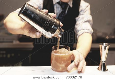 Bartender is making cocktail at bar counter , toned image