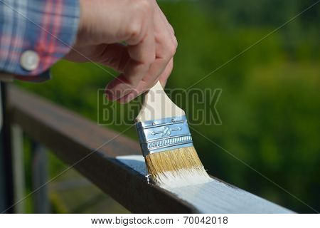 Man painting a guard rail on a balcony