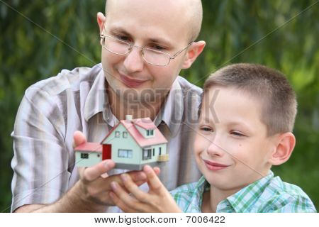 father and son keeping in their hands wendy house. focus on father's face