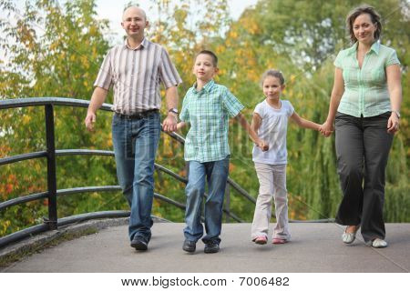 family with two children walking on bridge in early fall park. family is handies. focus on little bo
