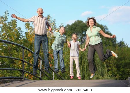 joyful family with two children is jumping on a bridge. family is handies.