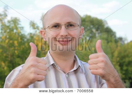 smiling man in early fall park with thumbs up gestures