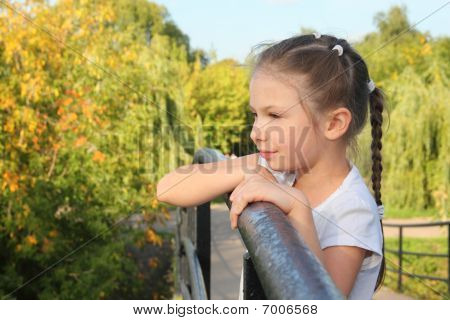 little girl is lean elbow on bridge fence and looking forward