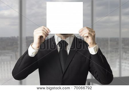 Businessman Hiding Face Behind Paper