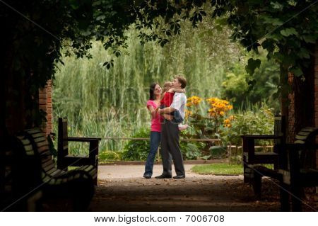 Parents and little girl in summer garden in plant tunnel. Man holds girl on hands. Horizontal format