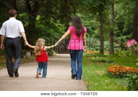Los padres junto con la hija a pie en el jardín de verano. Deje de mantener lejos de las manos.
