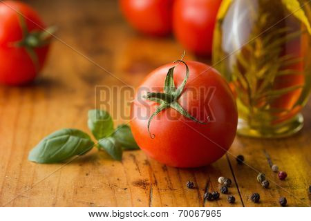 Tomatoes, basil, olive oil and  peppercorns on a wooden table